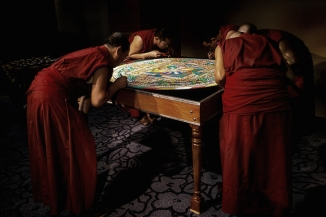 The monks putting the finishing touches on the nearly completed mandala.