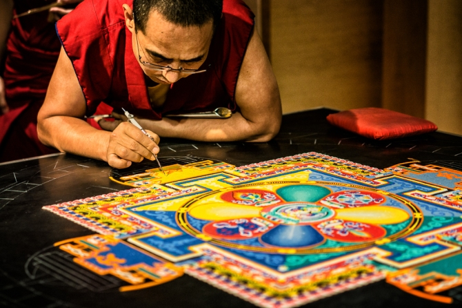 A monk traces guidelines for the next image in the yellow sand with a stylus.