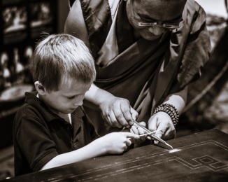 A monk demonstrates the process to a young visitor on the community sand painting.