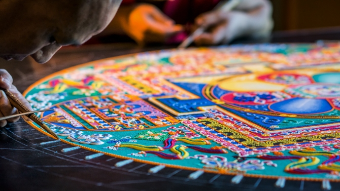 A monk lays the initial lines of the outer lotus petal ring.