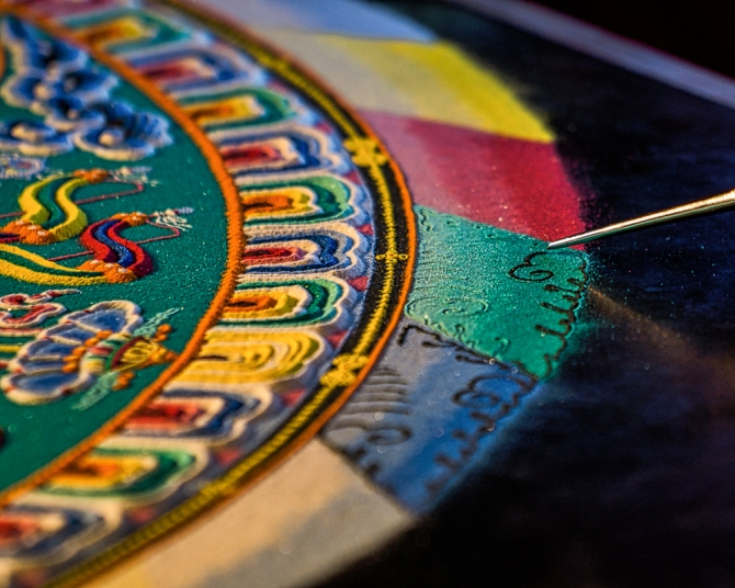 The three outer rings surround the mandala. The outmost ring represents flames of various colors. The black and yellow ring represent a three dimensional cosmic dome that surrounds the mandala. The innermost of the three rings consists of lotus petal designs.